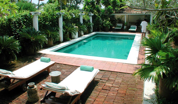 The Sun House Sri Lanka outdoor pool loungers surrounded by greenery