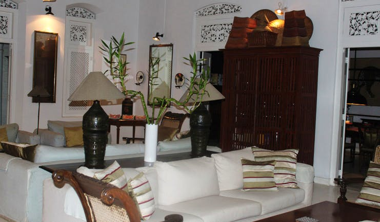The Sun House Sri Lanka sitting room with sofas and white carved vents