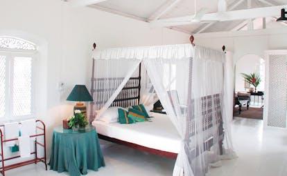 The Sun House Sri Lanka white bedroom exposed beams four poster bed white drapes