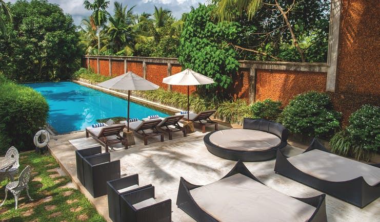 Tamarind Hill Sri Lanka pool sun loungers umbrellas patio greenery