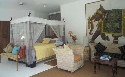 Taprobane Island Sri Lanka bedroom four poster bed sitting area large traditional elephant painting