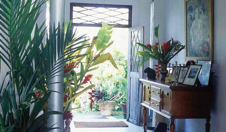 Taprobane Island Sri Lanka entrance porch dresser with antiques paintings and tropical flowers