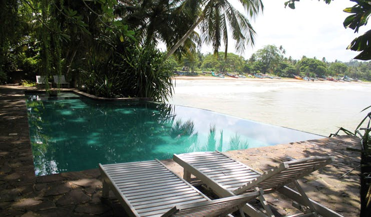 Taprobane Island Sri Lanka outdoor pool trees loungers next to beach