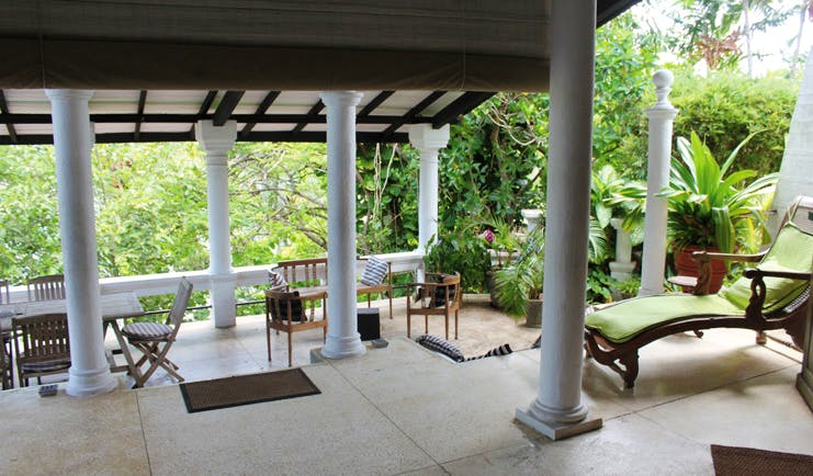 Taprobane Island Sri Lanka patio seating area columns loungers and tropical plants