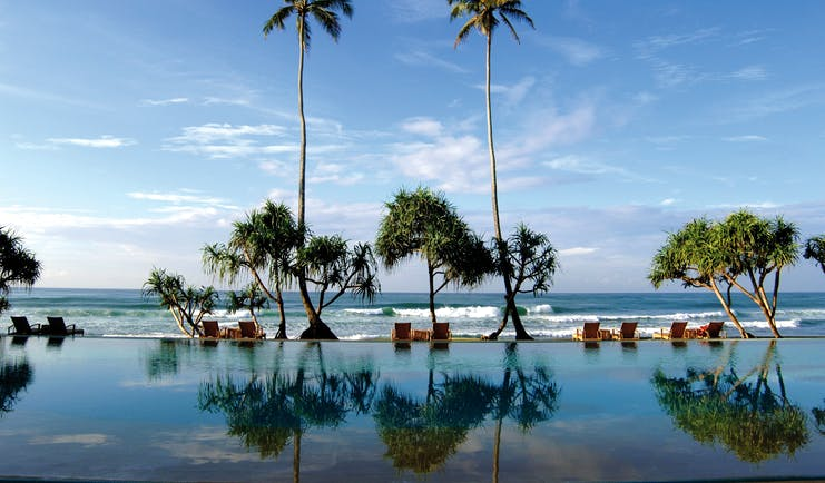 Outdoor infinity pool leading onto beach with palm trees and sunloungers