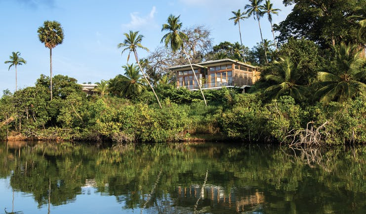 Tri Lanka Sri Lanka hotel building overlooking lake surrounded by trees and nature