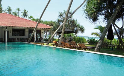 Weligama Bay Resort Sri Lanka poolside with loungers and sea view