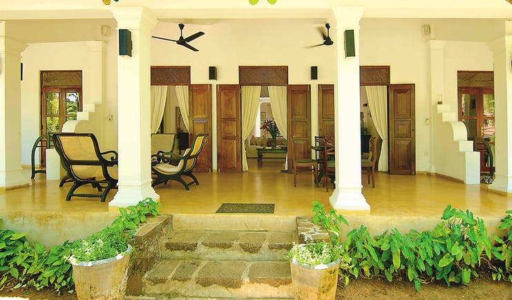 Why House Sri Lanka veranda covered outdoor seating area chairs columns trees