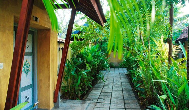 Ayurveda Pavilions Sri Lanka exterior yellow building painted doors stone path greenery