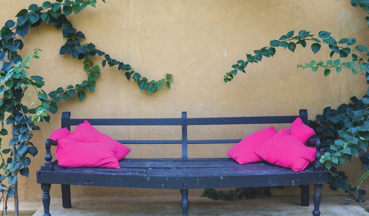 Casa Heliconia Sri Lanka bench outdoor seating area pink cushions green leaves