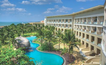Heritance Negombo Sri Lanka exterior hotel building pool trees lawn ocean in background