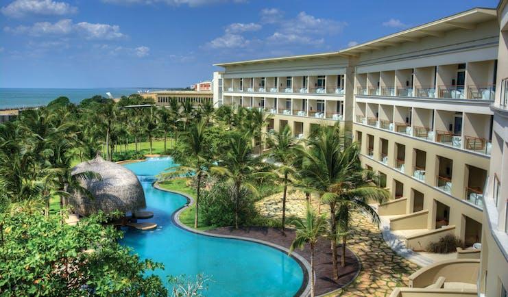 Heritance Negombo Sri Lanka exterior hotel building pool trees lawn ocean in background