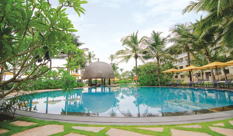 Heritance Negombo Sri Lanka pool umbrellas sun loungers trees hotel in background