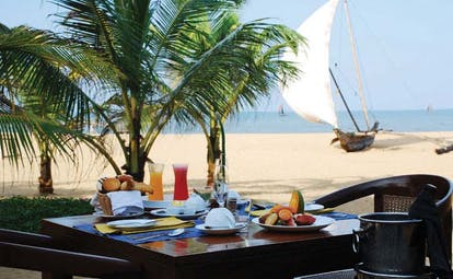 Jetwing Beach Sri Lanka beach dining table set for breakfast for two beach boat and sea in background