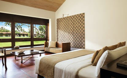 Jetwing Lagoon bedroom with large double bed, coffee table and large windows