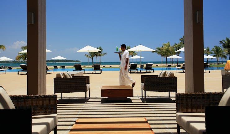Amaya Beach Resort Sri Lanka pool terrace chairs umbrellas waiter carrying drink