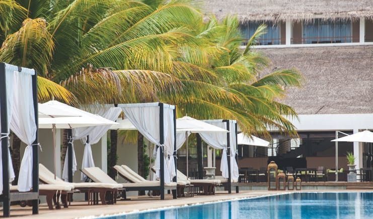 Anilana Pasikuda pool, infinity pool overlooking sea, beach cabanas, palm trees, lawn