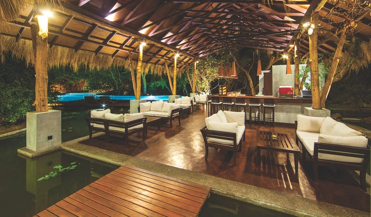 Jungle Beach bar, thatched structure beside pool with sofas and tables, soft lighting