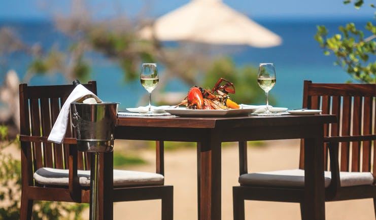 Jungle Beach beach dining, table set with seafood and wine on sand near to beach