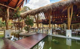 Jungle Beach open air resturant with thatched covering, placed beside pond, tables and chairs