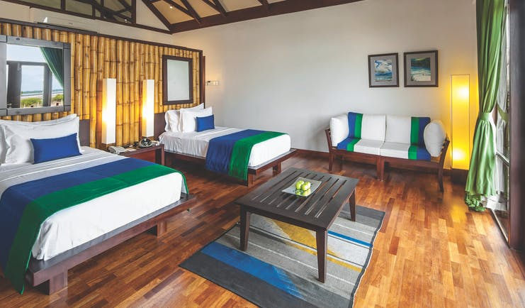 Jungle Beach twin room, two beds, sofa, wooden floor, balcony access, bright modern decor