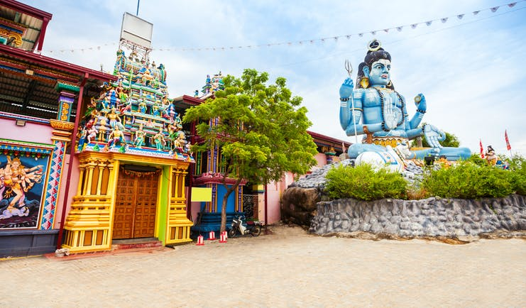Koneswaram Temple exterior, colourful architecture, large blue god statue