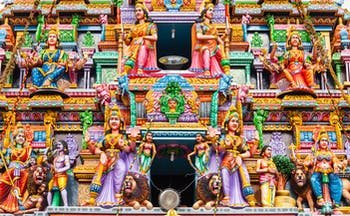 Pathirakali Amman Hindu temple exterior close up, bright vibrant carvings, statues of women, lions, colourful decoration