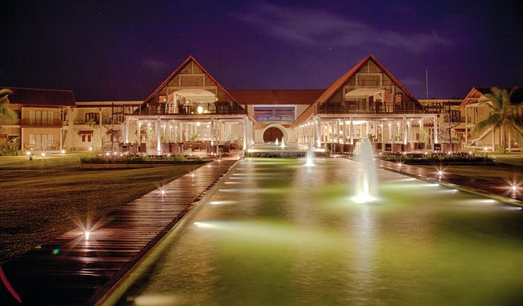Exterior of hotel at night with fountains in front