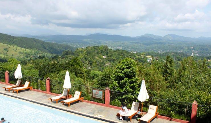 Amaya Hills Sri Lanka outdoor pool sun loungers umbrellas palm covered hills