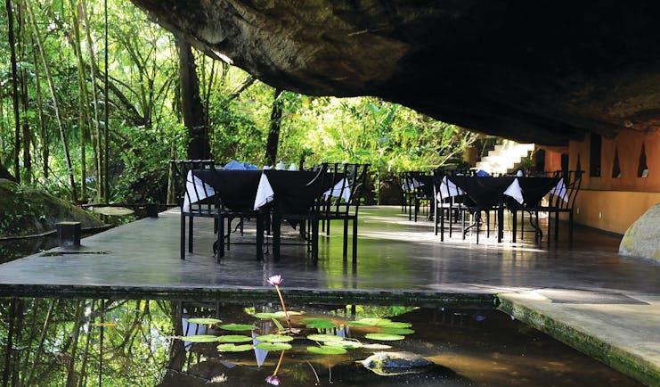 Boulder Garden dining outdoors under boulder rock formation, beside pond