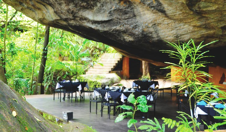 Boulder Garden restaurant outside placed underneath boulder rock formation, black tables and chairs on patio