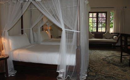 Ceylon Tea Trail Sri Lanka bedroom four poster bed sofa and large window