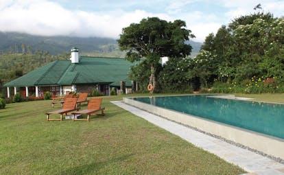 Ceylon Tea Trail Sri Lanka outdoor swimming pool loungers bungalow and mountain view