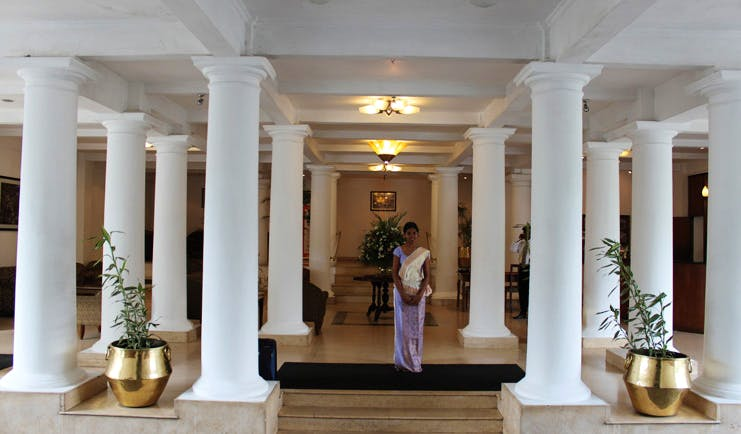Hotel Suisse Sri Lanka lobby with white columns and member of staff
