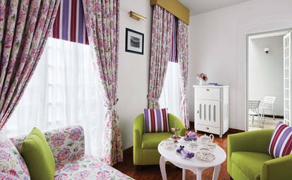 Magnolia cafe with pink and green colour scheme, draping curtains and arm chairs