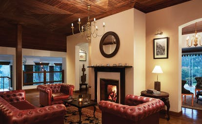 Lobby area with arm chairs, fireplace, chandelier and lampshades