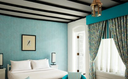 Superior bedroom with blue colour scheme, large double bed and draping blue curtains