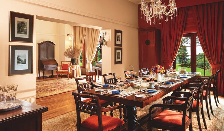 Jetwing Warwick Gardens dining room, table set for dinner, draped curtains, chandelier, grand decor