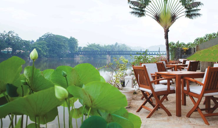 Mahaweli Reach Hotel riverside terrace, tables and chairs overlooking river