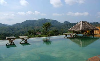 Rainforest Edge infinity pool overlooking mountains, cabana and chairs in the water