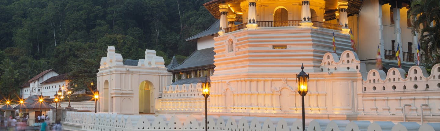 Exterior evening shot of the Temple of the Sacred Tooth Relic, white buildings lit up by lanterns