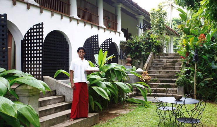 The Kandy House Sri Lanka Black Raja Suite exterior staff member with tray garden seating area