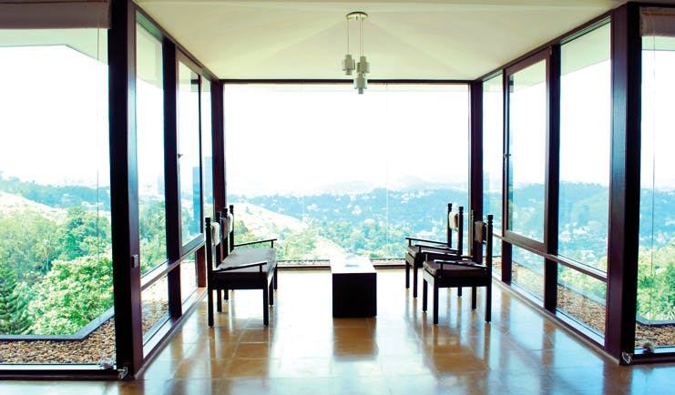 Theva Expressions Sri Lanka seats in lobby with panoramic forest views