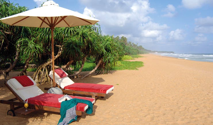 Aditya Resort beach with loungers and cocktails