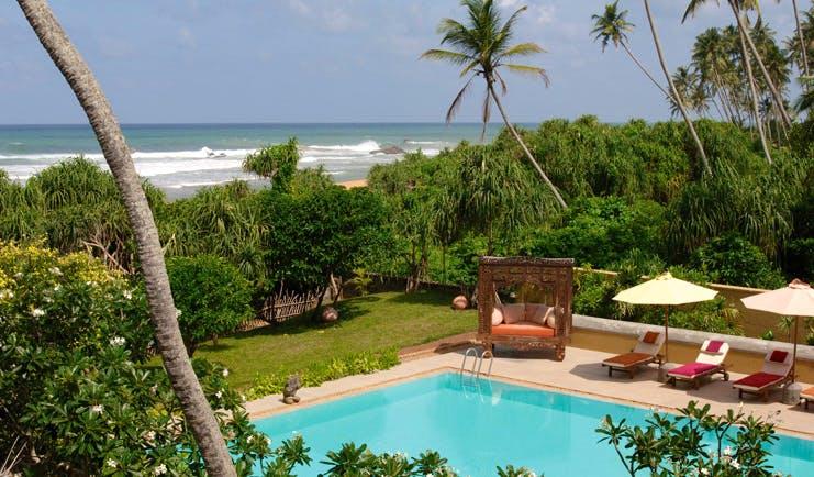 Aditya Resort outdoor pool with loungers cabana garden and sea view
