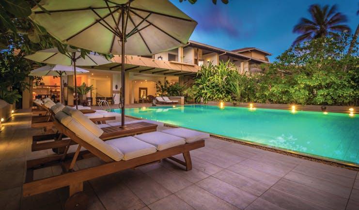 Aditya Resort poolside. sun loungers, umbrellas
