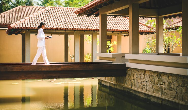 Anantara Kalutara Sri Lanka spa exterior buildings walkway over water female spa worker