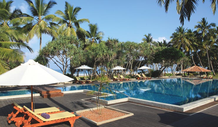 Avani Bentota Sri Lanka poolside sun loungers umbrellas beach in background