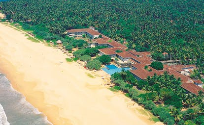 Aerial view of hotel and beach with greenery surrounding it and a beach nearby