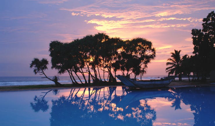 Heritance Ahungalla Sri Lanka poolside outdoor pool with traditional wooden boat at sunset